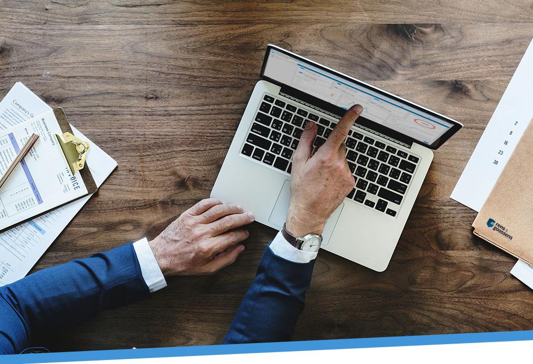belastingadviseur in pak wijst met zijn vinger naar het dashboard op zijn laptop